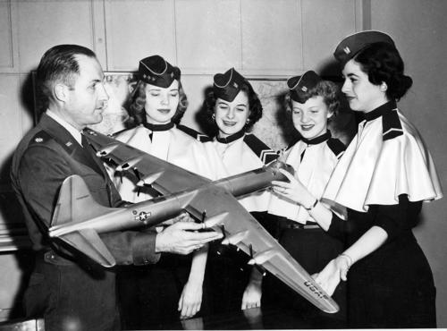 Four women of the Angel Flight Program are shown a model bomber by a male Air Force ROTC pilot at the University of Omaha. All of the persons appear to be white., UNO Libraries' Archives & Special Collections