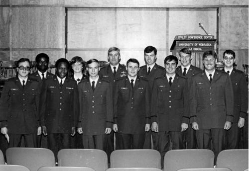 Twelve newly commissioned members of the Air Force ROTC stand for a photo at the University of Nebraska at Omaha. Nine appear to be white men, two appear to be black men, and one appears to be a white woman. All are in uniform., UNO Libraries' Archives & Special Collections
