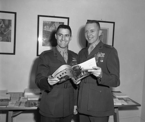 Two marine bootstrappers are smiling for a photo. They appear to be white and looking at a booklet together at the University of Omaha., UNO Libraries' Archives & Special Collections