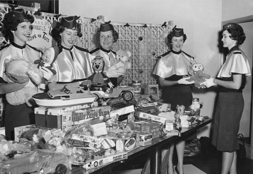 A group of five women of the Air Force ROTC Angel Flight program work together at the 'Toys for Tots' organization at the University of Omaha. The women all appear to be white., UNO Libraries' Archives & Special Collections