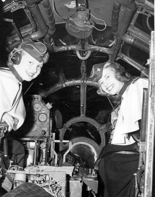 Two women pilot-members of the University of Omaha's Air Force ROTC Angel Flight program aboard an airplane. The women appear to be white and are smiling for the photograph., UNO Libraries' Archives & Special Collections