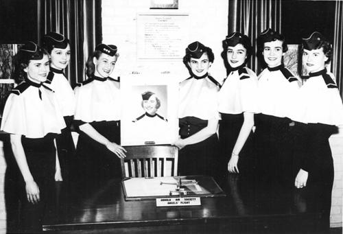 A black and white photo taken at the municipal University of Omaha. There are seven women of the Air Force ROTC who were members of the nation's first Angel Flight. The women all appear to be white and in the middle they are holding a photograph of another member., UNO Libraries' Archives & Special Collections