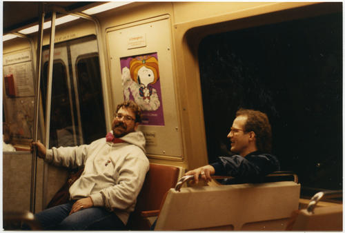 Pat Phalen (on left, wearing a grey sweatshirt) and Tim Crosen (both Caucasian men) riding on public transportation in the Washington, D.C. area., UNO Libraries' Archives & Special Collections