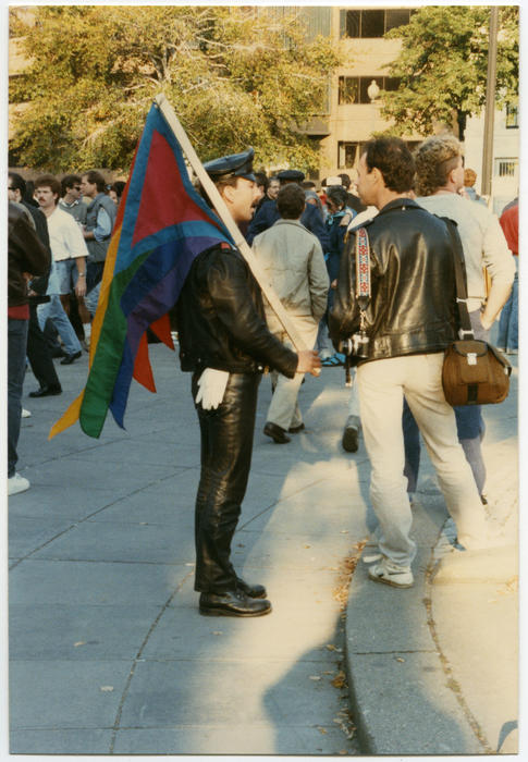 Two unidentified Caucasian people (one is dressed head-to-toe in black leather and holding multicolored flag) talking to one another while standing in a large crowd at the Second National March on Washington for Lesbian and Gay Rights in Washington D.C. on October 11, 1987., UNO Libraries' Archives & Special Collections
