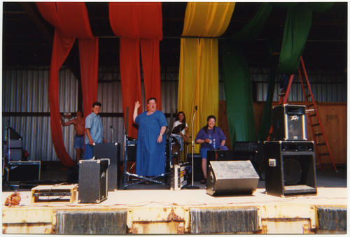 An image of unknown band (four unidentified Caucasian people) setting up their instruments and rehearsing on the Soar with PRIDE block party stage in Omaha, Nebraska while workers (one unidentified Caucasian person and one unidentified person of unknown ethnicity) set up the stage decorations consisting of large panels of rainbow colored fabric (2 panels of red, followed by 2 panels of orange, followed by 2 panels of yellow, and so on) draped to form a ceiling and backdrop., UNO Libraries' Archives & Special Collections