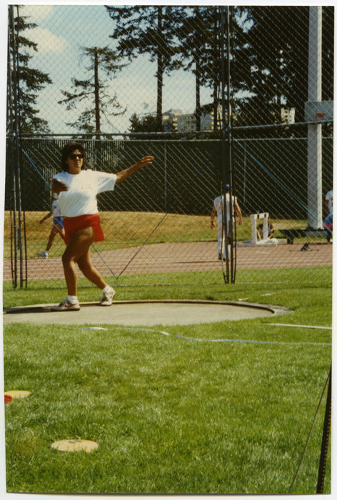 An unidentified person of unknown ethnicity wearing red shorts, winding up in preparation to throw discus at Gay Games II., UNO Libraries' Archives & Special Collections