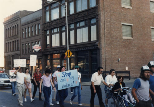 "A group of people marching in the Downtown Omaha, carrying the signs. One of the signs reading ""Stop anti-gay violence!"", UNO Libraries' Archives & Special Collections"