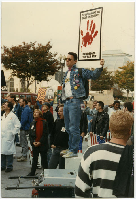 "A large group of unidentified Caucasian and African American people, some holding indecipherable signs, with one unidentified person standing above the crowd while holding a sign, ""The Government Has Blood On Its Hands, One AIDS Death Every Half Hour"" at the Second National March on Washington for Lesbian and Gay Rights in Washington D.C. on October 11, 1987., UNO Libraries' Archives & Special Collections"