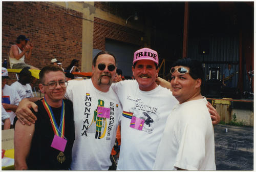 A group photo at the Soar with PRIDE parade and block party in Omaha, Nebraska with four people with their arms around each other while smiling for the camera: one unidentified Caucasian person, Pat Phalen (a Caucasian person wearing sunglasses), Dick Brown (a Caucasian person wearing pink Pride ball cap), and one unidentified person of unknown ethnicity., UNO Libraries' Archives & Special Collections