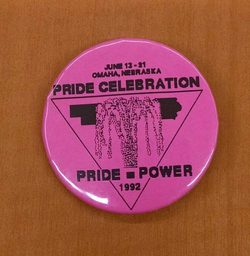 "Photograph of a pink button for the 1992 Pride Week Celebration in Omaha, Nebraska. The button reads ""Pride celebration"" and ""Pride = Power."" The celebration took place June 13-21, 1992., UNO Libraries' Archives & Special Collections"