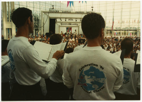 "View from behind of unidentified Caucasian and probable Latino American people performing in ""Celebration '90 Festival Chorus"" while wearing long-sleeved t-shirts with text, ""Celebration '90 Festival Chorus"" and logo consisting of Earth (globe), musical notes on ""moving"" staff, and purple triangle (possible twin mountain peaks) at Gay Games III in Vancouver, British Columbia, Canada., UNO Libraries' Archives & Special Collections"