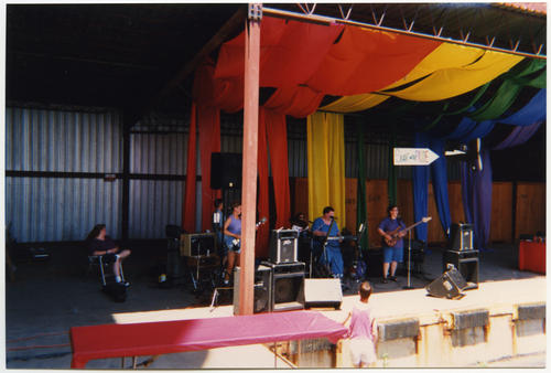 An image of unknown band (four unidentified Caucasian people) rehearsing with their instruments on the Soar with the PRIDE block party stage in Omaha, Nebraska while one unidentified Caucasian person observes while seated nearby (on stage, just off to one side). The stage decorations consist of large panels of fabric draped to form a rainbow ceiling and backdrop., UNO Libraries' Archives & Special Collections