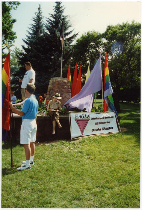 "An image of guest speaker Susan Koenig, from the National Organization for Women (former president of the Omaha Chapter from 1990 to 1991) writing in a notebook, Patrick (Pat) Phalen (ICON Emperor VI) standing near her on folding tables, and one unidentified Caucasian person holding a PRIDE rainbow flag. Flags each color of the rainbow (made by Terry Sweeney and Patrick (Pat) Phalen) and a banner reading ""EAGLE - Employee Association for Gays and Lesbians, a US West Resource Group, Omaha Chapter"" also at the PRIDE Parade and Festival held at Turner Park in Omaha, Nebraska.  [NOTE: Every year, in July, the Imperial Court of Nebraska (ICON) elects and Emperor and Empress. These individuals are the public face of the organization both in town and across the nation. Patrick (Pat) Phalen was elected as Emperor VI in 1985.], UNO Libraries' Archives & Special Collections"