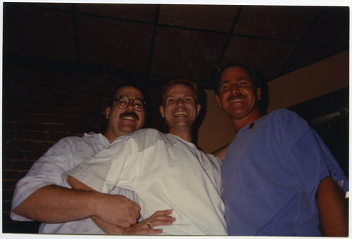 A low angle image of Pat Phalen, Michael Groh, and Dick Brown (Left to Right)standing and posing together with huge smiles on their faces. Pat is standing behind Michael, with his arms wrapped around him., UNO Libraries' Archives & Special Collections