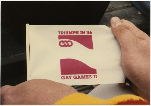 "Pat Phalen holding Gay Games II miniature Flag (white with red text, ""Triumph in '86"" and ""Gay Games II"" plus Games' logo in red)., UNO Libraries' Archives & Special Collections"