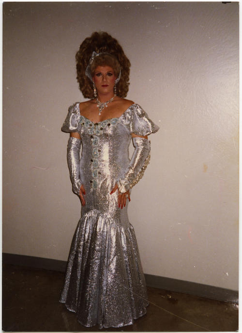 Nici Leigh posing in front of a white wall wearing full makeup and an off-shoulder, floor length, mermaid style silver lame gown with coordinating opera length silver lame fingerless gloves and head scarf. Nici Leigh is the name Michael Groh used when he performed drag., UNO Libraries' Archives & Special Collections