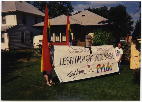 "An image of Patrick (Pat) Phalen and Terry Sweeney smiling for the camera in an unidentified back yard while holding a large banner that reads ""Omaha's 7th Annual Lesbian and Gay PRIDE Parade, 'Together in Pride'"" and flanked by two large rainbow PRIDE flags. Terry Sweeney and Patrick (Pat) Phalen made the banner and flags for the 1991 PRIDE Parade and Festival in Omaha, Nebraska., UNO Libraries' Archives & Special Collections"