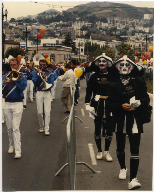 Unidentified Caucasian people playing instruments in a marching band walking with the Sisters of Perpetual Indulgence at Gay Games II. The Sisters of Perpetual Indulgence are all unidentified people of unknown ethnicity wearing black & white female cheerleader uniforms with nun's habit and full face paint or makeup., UNO Libraries' Archives & Special Collections