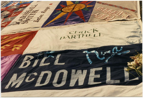 Close-up image of NAMES Project AIDS Memorial Quilt at the 1987 unveiling on the National Mall in Washington, D.C. showing panels made in honor of Chuck Barthell and Bill McDowell. [Each individual 3' by 6' quilt panel is the size of a human grave]., UNO Libraries' Archives & Special Collections