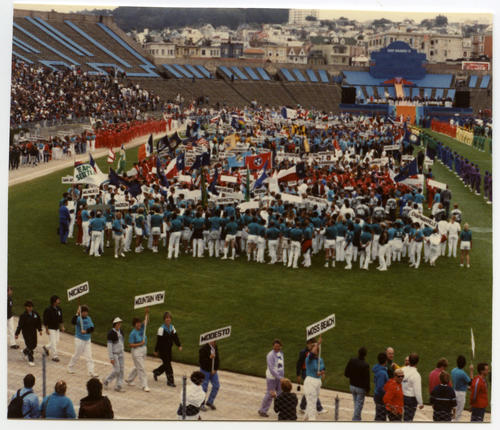 Parade of States with California's procession in the foreground and Assembly of State(s) in a group on the field during the Gay Games II opening ceremony., UNO Libraries' Archives & Special Collections