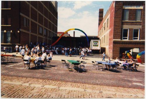 A wide shot image of the Omaha, Nebraska, Pride Parade Festival block party on Jones Street between 14th & 15th Streets while events are just getting started, possibly before the parade kick-off., UNO Libraries' Archives & Special Collections