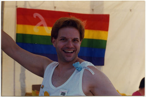 A close up image of Mike Groh with outstretched arms and an open mouth smile with a Pride rainbow flag hanging in the background. Groh moved from Omaha to San Diego., UNO Libraries' Archives & Special Collections