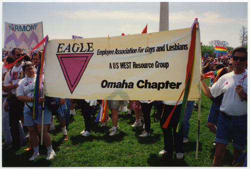 Two unidentified Caucasian people holding outstretched Eagle Banner (Employee Association for Gays and Lesbians, A US West Resource Group, Omaha Chapter) at the 1993 March on Washington for Lesbian, Gay, and Bi Equal Rights and Liberation (The March)., UNO Libraries' Archives & Special Collections