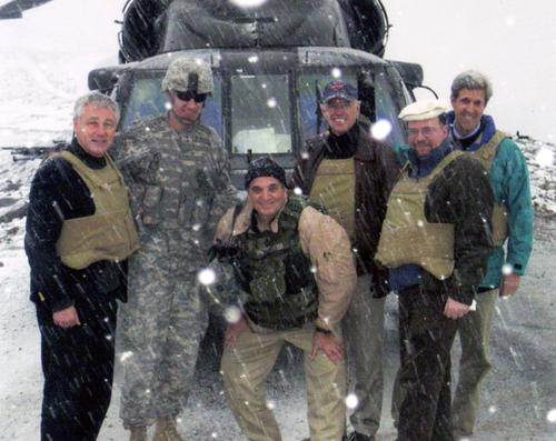 Photograph of Senators Hagel and Kerry, their military escort, and helicopter crew in front of helicopter that was downed in the mountains of Afghanistan because of a snow storm., UNO Libraries' Archives & Special Collections