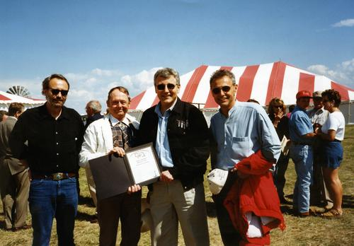 Tom Hagel, Mayor Gerry Osborne, mayor of Ainsworth, Chuck Hagel, and Mike Hagel. The mayor is presenting Senator Hagel with his little league box scores during the festivities around the Cattleman's Ball near Ainsworth, Nebraska., UNO Libraries' Archives & Special Collections